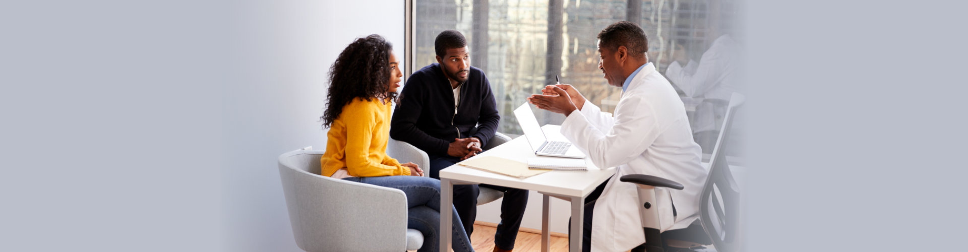 Couple Having Consultation With Male Doctor