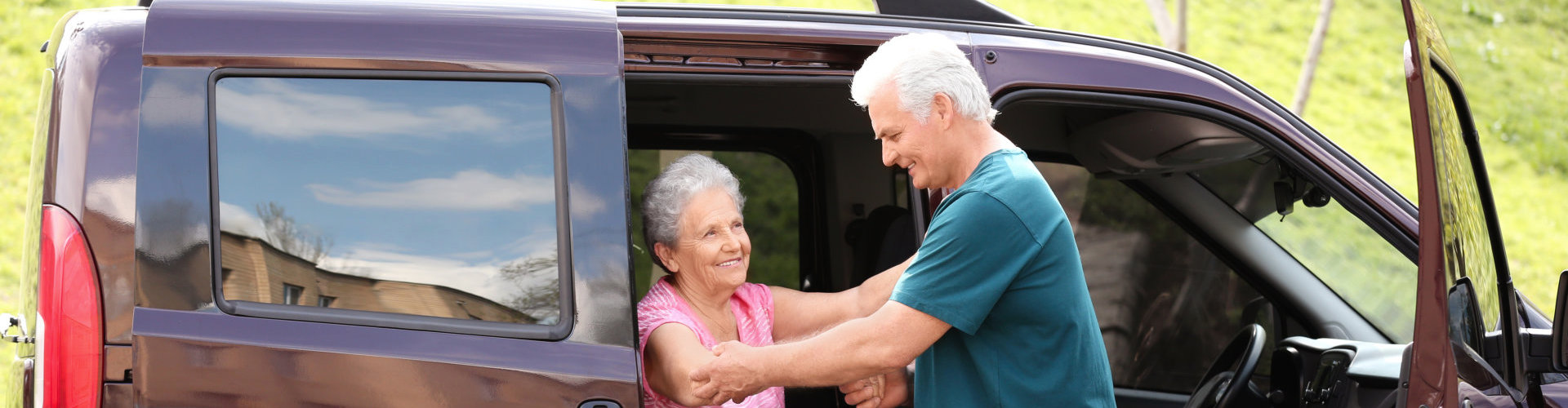 old man assisting to his wife to get off the van