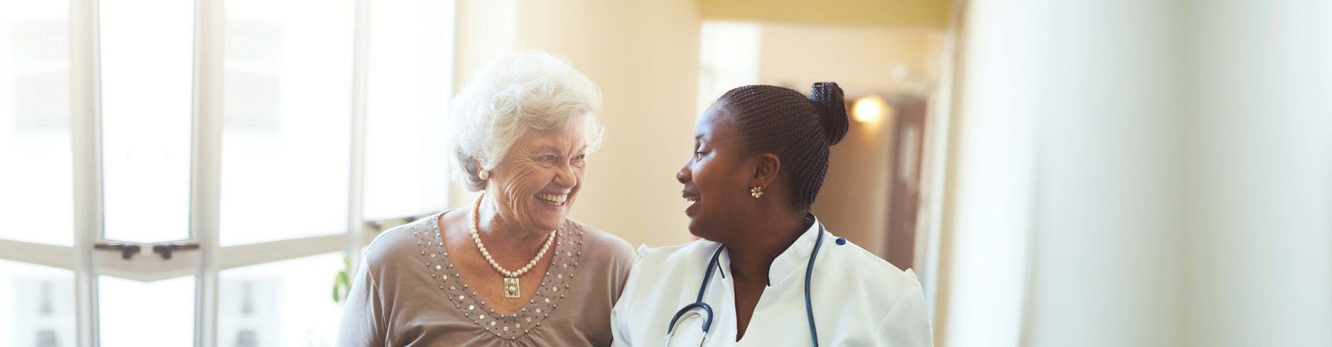 african nurse smiling with her old woman patient